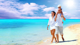 stock photo of family vacations  - View of happy young family having fun on the beach - JPG