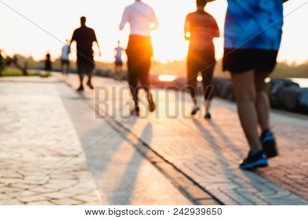 poster of Blurred Group Of Runner Are Running In Park At Evening Sunset.