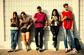 Young teenage friends chilling out together and using smartphones poster