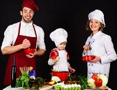 Child With Parents Cooking At Kitchen Table. Happy Loving Family Preparing Dinner Together.cheerful  poster