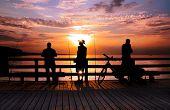 Three Angler standing on a bridge in the sunrise, back lite,