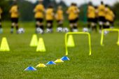 Football Training Session. Soccer Balls, Pylons, Cones, Marks And Training Hurdles On Grass Pitch. Y poster