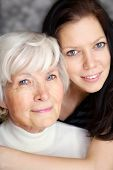 Grandmother and granddaughter portrait, embraced  and smiling at camera