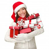 Christmas shopping woman holding many Christmas gifts in her arms wearing santa hat and winter cloth