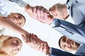 Below view of four people handshaking
