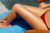 Woman Apply Sun Cream Protection Cream On Her Smooth Tanned Legs. Beautiful Legs Outdoors By On Whit poster