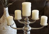 Beautiful vase and candles on rustic silver candelabra in stylish home