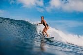 Surf Woman At Surfboard Ride On Wave. Woman In Ocean During Surfing. Surfer And Ocean poster