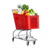 picture of grocery-shopping  - Red shopping cart with grocery items - JPG