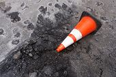 Broken Weathered Street Astroturf Pot Hole With White Striped Orange On Its Side poster