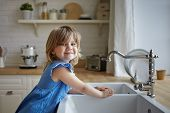 Charming Little Girl In Blue Dress Washing Hands In Kitchen. Cute Female Kid Looking And Smiling At  poster