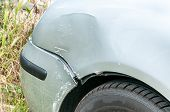 Damaged Car. Front Side Near Headlight Of Broken And Damaged Silver Car Wreck In Crash Accident With poster