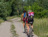 Two Pretty Girls Cycling In The Wild Nature On Dirt Road. Bikes Cycling Girl. Girl Rides Bicycle. Bl poster