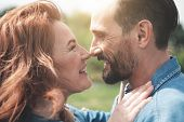 Close Up Profile Of Cheerful Mature Loving Couple Touching Their Noses And Smiling. They Are Looking poster