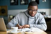Focused Millennial African American Student In Glasses Making Notes Writing Down Information From Bo poster