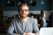 Smiling Redhead Man With Laptop Looking At Camera In Cafe, Happy Millennial Guy In Glasses Posing In poster