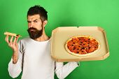 Pizza. Handsome Sexy Bearded Man With Serious Face Eating Pizza. Man Eating Pizza And Holds Box. Hip poster