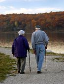 image of old couple  - older couple with canes walking along path next to lake - JPG