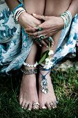 boho fashion details woman hands and bare feet on grass with lot of  bohemian style jewrly rings bra poster