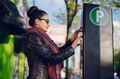 Beautiful Young Woman Pays For Parking In Meter On The Street poster