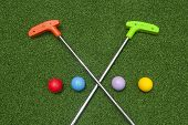 Two Mini Golf Putters Are Crossed With Colorful Mini Golf Balls On Green Synthetic Grass poster