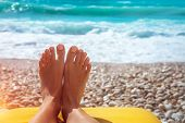 Closeup photo of a womens feet with nice pedicure lying down on stony seashore, conceptual photo of poster