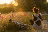 Summer Sunset In Countryside. Sunset Light In Countryside. Girl Sitting In Field In Sunset. Girl Rel poster
