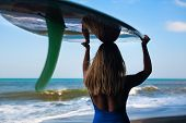 Girl In Bikini With Surfboard Walk On Black Sand Beach. Surfer Woman Look At Sea Surf And Water Pool poster