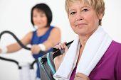 Mature women using gym equipment