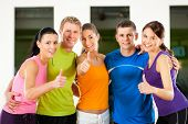 Group of five people exercising in gym or fitness club