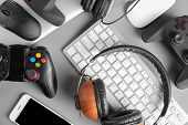 Gamepads, Mice, Headphones And Keyboard On Table poster