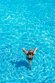 woman relaxing in infinity pool at luxury resort spa retreat. Beautiful unrecognizable woman sunbath poster