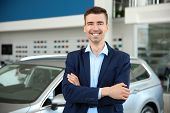 Portrait Of Young Salesman In Car Dealership poster