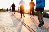 Blurred Group Of Runner Are Running In Park At Evening Sunset. poster