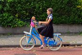 Portrait Of A Girl In A School Uniform Who Rides A Bicycle. The Girl Goes To School With Her Doll. B poster