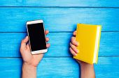 Phone Versus Book. A Man Is Holding A Yellow Book And A Phone On A Blue Wooden Background. The Choic poster