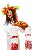 Beautiful ukrainian young hospitable woman in garland and native costume by tradition holding embroi