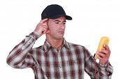 Puzzled tradesman staring at his multimeter