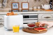Male Hand Reaches For A Crunchy Toast With Raspberry Jam. White Toaster, Glass Of Orange Juice, Bowl poster