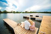Romantic Date Surprise. A Young Guy And A Girl On A Wooden Pier. Hug And Kiss While Sitting On The P poster
