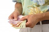 stock photo of pesos  - Closeup of unrecognizable male tourist counting handful of pesos Mexican currency - JPG