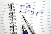 Blauwe en zilverkleurige pennen op de opmerking boek