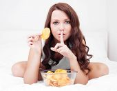 pretty woman eating potato chips in bed at home with finger on her lips