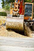 Orange excavator at work in a large sandpit