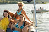 Young women sunbathing on boat sailing on lake