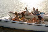 Group of women and men navigating motorboats summer lake