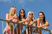 Beautiful women in bikinis and sunglasses smiling with drinks