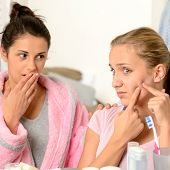 stock photo of puberty  - Young teenager and her friend squeeze pimple in the bathroom - JPG