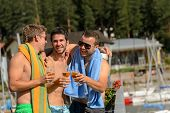 Young guys toasting with beer enjoying summer in swimsuits