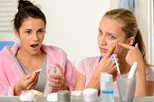 stock photo of puberty  - Young teenager with acne problem in the bathroom with friend - JPG